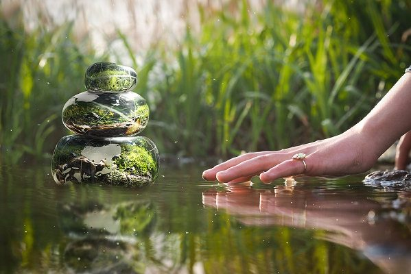 Transparent stones in water Zen pyramid. Stones of the volume inside the stones nature flowers. Children's or woman's hand above the water surface. Concept - peace of mind inner peace harmony